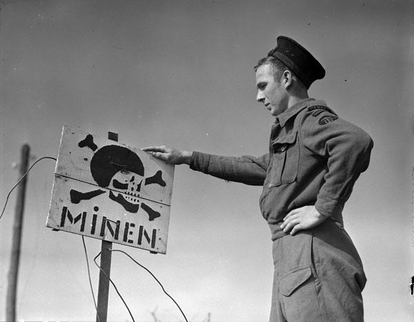 Photo of Seaman looking at a Mine Warning Sign