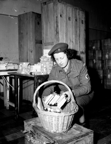 Photo of Nursing sister packing a basket of first aid guides in France.
