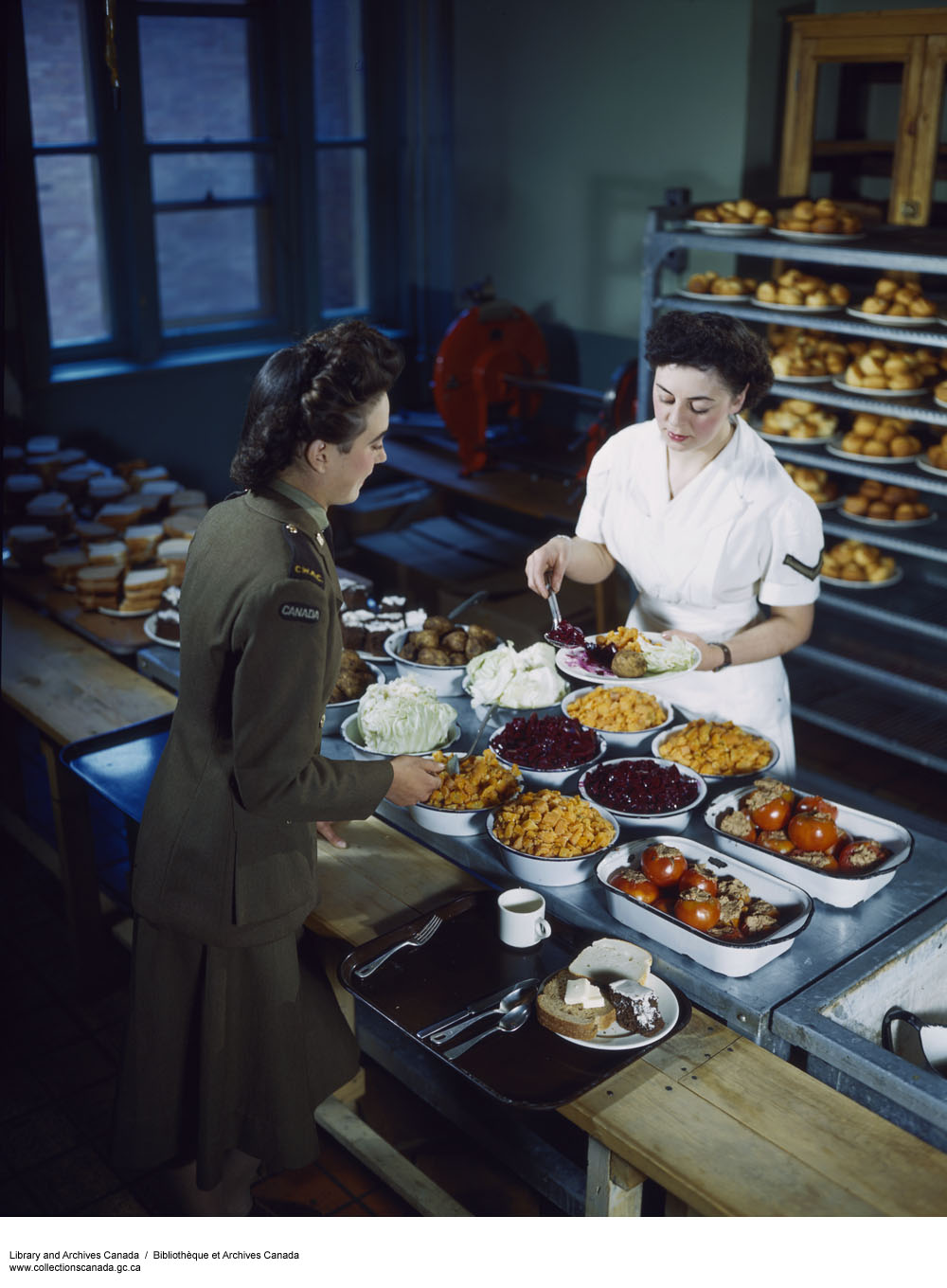 Photo of a CWAC cook serves a meal to her fellow CWAC.