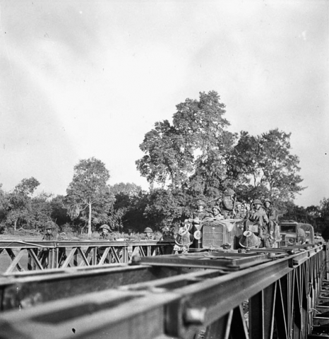 """Infantrymen of the Stormont, Dundas and Glengarry Highlanders crossing the Orne River on a Bailey bridge built by the Royal Canadian Engineers (R.C.E.) en route to Caen, France, 18 July 1944."" Photo: Ken Bell. Courtesy of Library and Archives Canada, 1967-052 NPC."