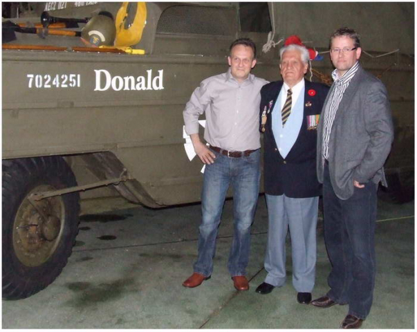 Mechanic Mario van Gerwen names a DUKW (known as a DUCK)  amphibious military truck after Donald Somerville in honour of his help in evacuating the 1st Airborne Division and for his role as an engineer, c. 2010. From left to right: Mario van Gerwen, Donald Somerville, and Goossen Foppen. Courtesy of the Canadian Military Engineers Association.