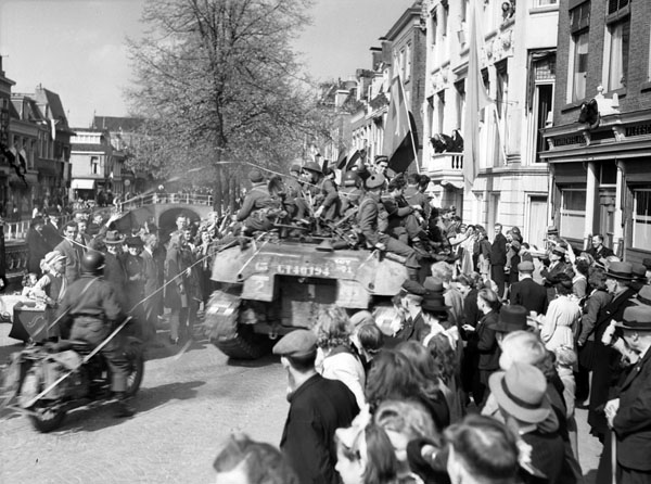"""Crowd welcoming The Stormont, Dundas and Glengarry Highlanders to Leeuwarden, Netherlands, 16 April 1945."" Photo: Donald Grant. Courtesy of Library and Archives Canada, 1967-052 NPC."