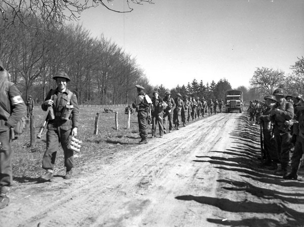 """Infantrymen of The North Nova Scotia Highlanders advancing near Dorterhoek, Netherlands, 8 April 1945."" Photo: Donald Grant. Courtesy of Library and Archives Canada,1967-052 NPC."