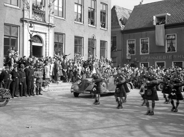 """Pipe bands of The Highland Light Infantry of Canada and The North Nova Scotia Highlanders arriving at a civic reception, Leeuwarden, Netherlands, 16 April 1945."" Photo: Donald Grant. Courtesy of Library and Archives Canada,1967-052 NPC."