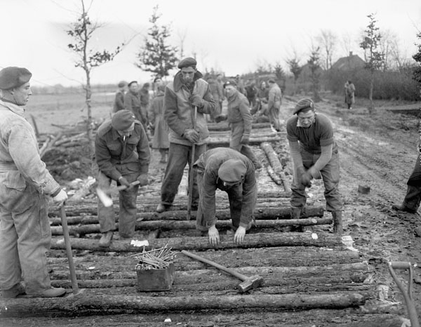 """Personnel of the Royal Canadian Engineers (R.C.E.) rebuilding a road to maintain the flow of supplies to units of the 1st Canadian Army advancing towards the Reichswald. Haps, Netherlands, 8 February 1945."" Photo: Ken Bell. Courtesy of Library and Archives Canada, 1967-052 NPC."