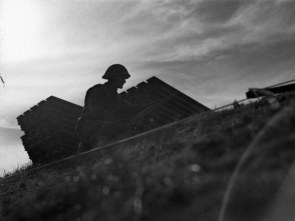 """""""Personnel de la 16e compagnie de campagne, Génie royal canadien (R.C.E.), construisant des pontons Bailey pour transporter les canons automoteurs M-10 du 3e régiment antichar, Artillerie royale canadienne (R.C.A.), de l'autre côté de l'Escaut, près de Terneuzen, Pays-Bas, 13 octobre 1944"""". Photo : Donald Grant. Avec l'autorisation de Bibliothèque et Archives Canada, 1967-052 NPC."""
