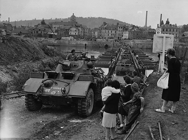"""General Motors 'Staghound' T17E1 armoured cars of the 18th Armoured Car Regiment (12th Manitoba Dragoons) crossing the Seine River."" Photo: Harold G. Aikman. Courtesy of Library and Archives Canada, 1967-052 NPC."