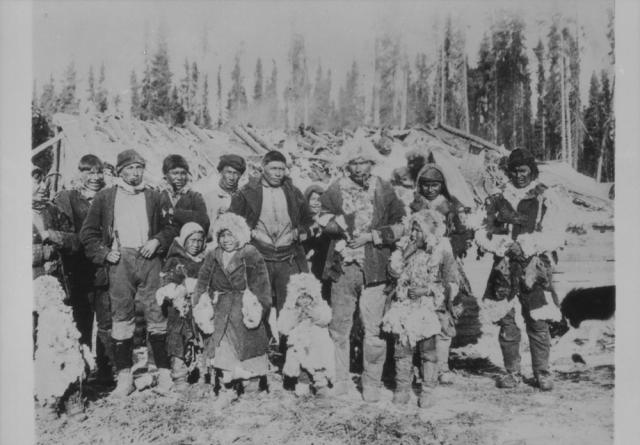 """""""Un groupe composé d'hommes et d'enfants cris, debout devant une structure inconnue dans le district de Kenora (anciennement le district de Patricia), dans le nord-ouest de l'Ontario"""" 1936. Avec l'autorisation de Bibliothèque et Archives Canada, 1936-271 NPC"""