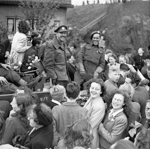 """Infantrymen of The West Nova Scotia Regiment in a Universal Carrier en route to Rotterdam are surrounded by Dutch civilians celebrating the liberation of the Netherlands."" May 1945. Photo: Barry Gilroy. Courtesy of Library and Archives Canada,1967-052 NPC."