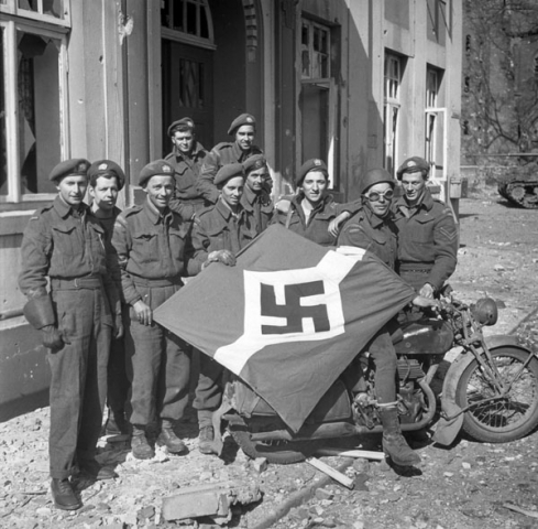 """Personnel of The Lake Superior Regiment (Motor) with a captured German flag, Friesoythe, Germany, 16 April 1945."" Photo: Alexander M. Stirton. Courtesy of Library and Archives Canada,1967-052 NPC."