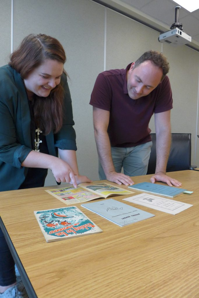 Project manager Alison Little and Curator Jay Young review records for an online exhibit.